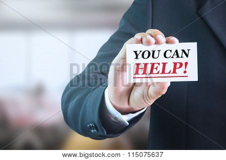 Businessman holding a white sign with the message you can help.