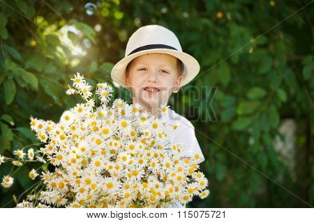 Portrait adorable boy in a hat with big white bouquet of camomiles