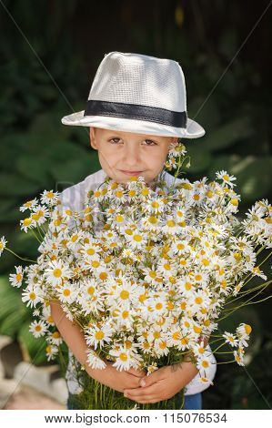 Portrait adorable boy in a hat with big white bouquet of camomiles.