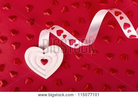 White Heart With Ribbon And Red Hearts On Red