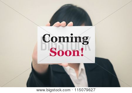 coming soon message on the card Held by women.