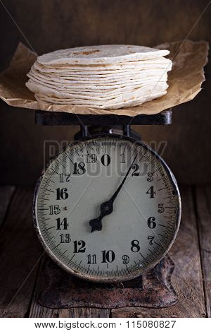 Stack of wheat tortillas on vintage kitchen scales