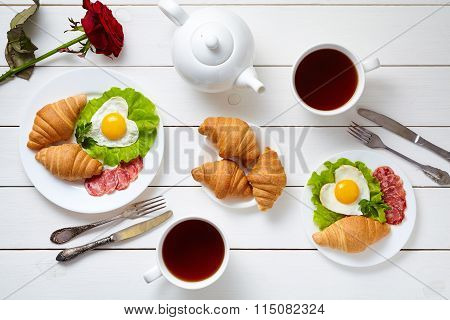 Romantic meal for two with heart shaped eggs, salad, croissants, rose flower and tea on white wooden