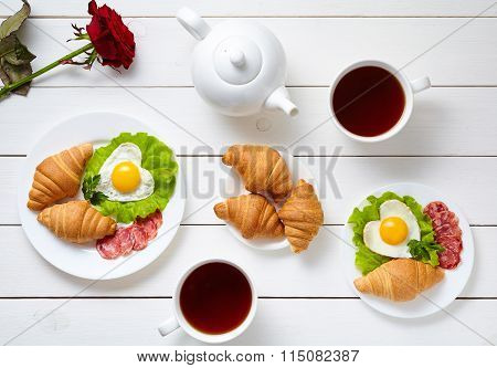 Romantic breakfast for Valentines Day with heart shaped eggs, salad, croissants, rose flower and tea