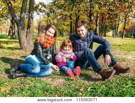 Happy Young Family In An Autumn Park