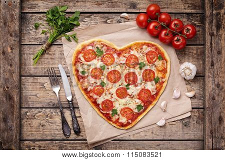 Heart shaped pizza margherita love concept for Valentines Day with mozzarella, tomatoes, parsley and