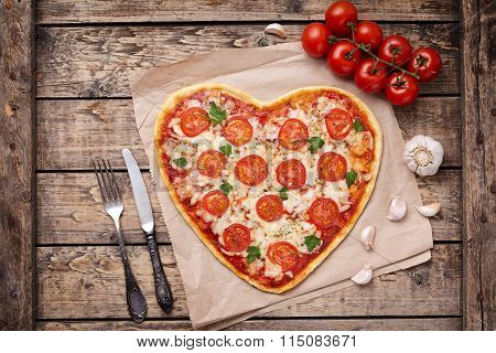 Vegetarian heart shaped pizza margherita with tomatoes, mozzarella, parsley and garlic on vintage wo