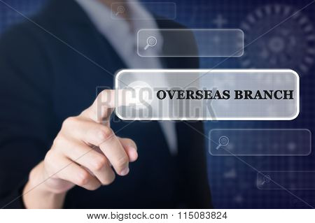 Businessman pressing a OVERSEAS BRANCH concept button.