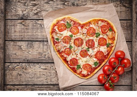 Heart shaped pizza margherita with tomatoes and mozzarella vegetarian meal on vintage wooden table b