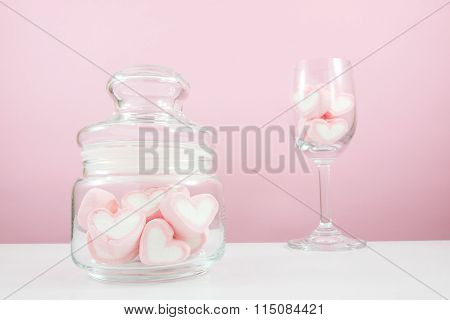 The lovely pink heart marshmallows in small glass jar and wine glass