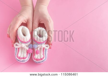 Female Hands Carefully Holing Baby Shoes
