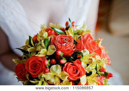 Wedding Gold Rings On A Red And Yellow Bouquet