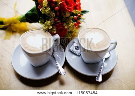 Two Cups Of Coffee On The Table And A Bouquet