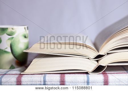 Pile Of The Opened Books On A Table