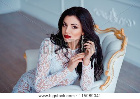 Perfect portrait of sexy young woman with red lips wearing seductive white dress sitting on luxury v
