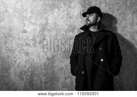Man In Vintage Cap And Coat Standing Near Old Wall