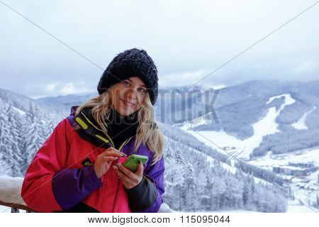 Smiling woman write a message in the mountains
