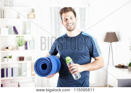 Handsome Fit Man Holding Mat And Bottle Of Water