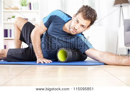 Athletic Guy Using Foam Roller In Exercise