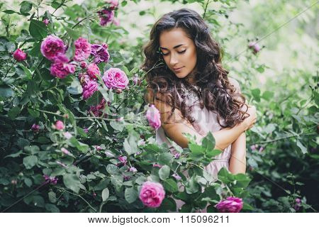 Girl with long curly hair in pink dress posing in the garden