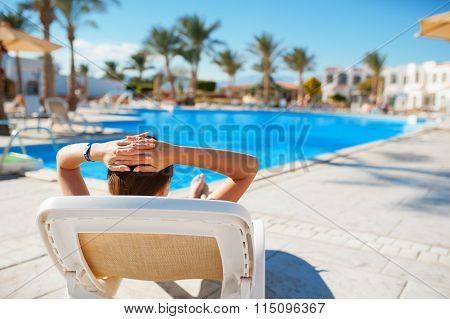 Woman Lying On A A Lounger And Looking The Pool