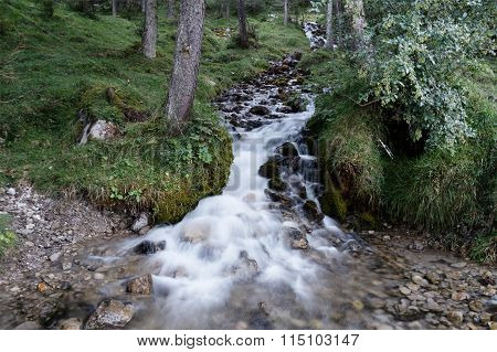 White cascades in a brook appearing rapid and soft