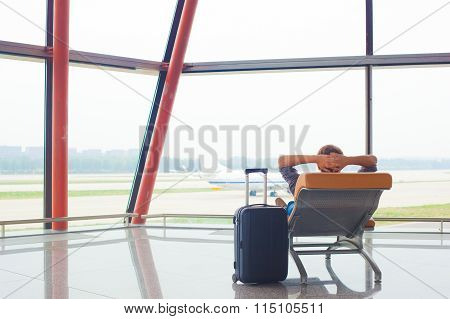 man waiting for his flight at the airport on lounge chair
