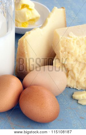 Dairy products on grunge blue background.  Includes milk, eggs, cheeses and butter.