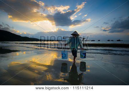 DANANG, VIETNAM - DECEMBER 30, 2015: People work in sunrise in My Khe beach, Da Nang, Vietnam.