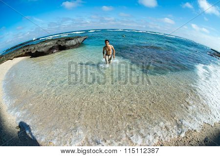 Young man enjoy in transparent beach in Ly Son island, Quang Ngai, Vietnam