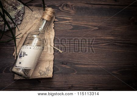 Message in a bottle with copy space on tropical  wooden background with sea shells
