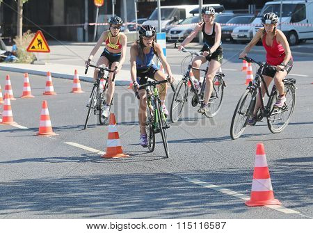 Four Young Woman Cycling In A Curve, Avoiding Cones