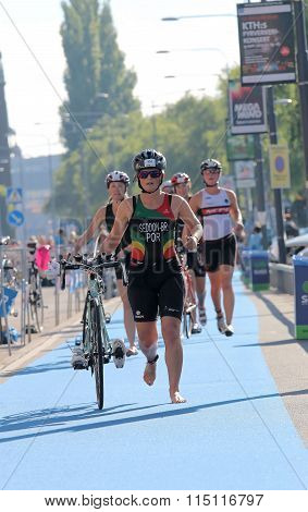 Many Woman Running Barefoot With Bicycle In The Triathlon Transition Zone