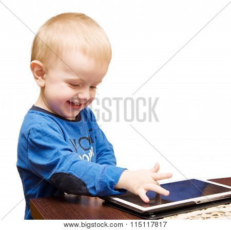 The Little Boy Laughs And Drives A Finger On The Tablet