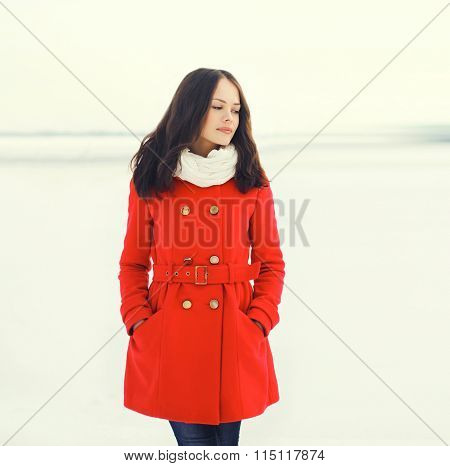 Beautiful Young Woman Wearing A Red Coat Over Snowy Field In Winter Day