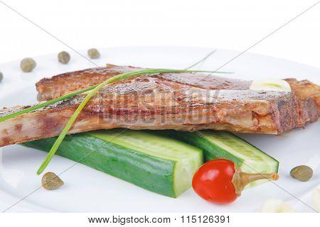 fresh grilled beef meat fillet on white plate with tomatoes and capers isolated  over white background . shallow dof