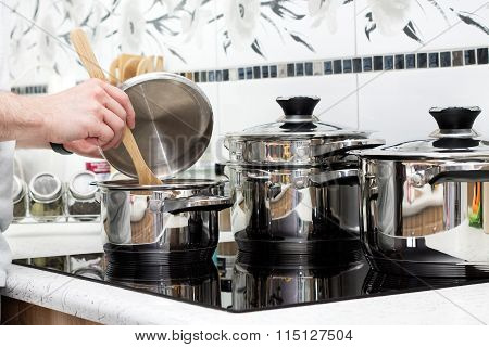 Man prepares dinner on modern induction cooker
