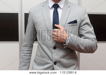 Man in gray suit with tie tie clip and handkerchief
