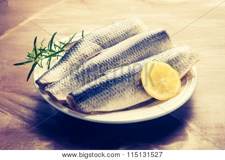 Vintage Photo Of Raw Herrings Fillets With Lemon And Rosemary