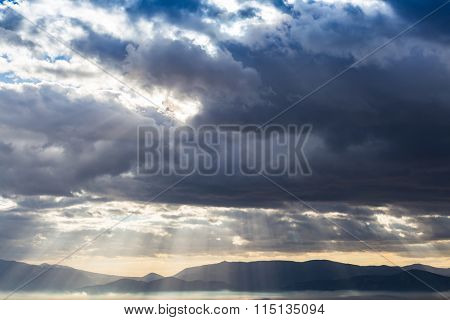 Dramatic heavy clouds above the landscape with sunrays coming through.