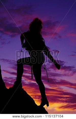 Silhouette Of A Woman Backpacking Reaching Down