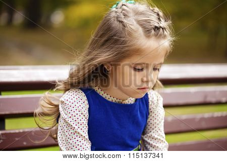 Sad little girl is sitting on the bench, autumn outdoor shoot