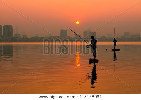 Fisherman in sunset in West Lake (Ho Tay).
