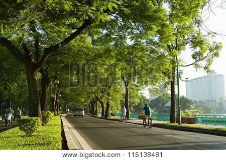 People walk and ride on Thanh Nien street in early morning in Hanoi, Vietnam.