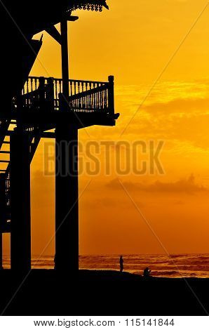 Silhouette Of Veranda At The Beach During Sunrise With People At Seaside