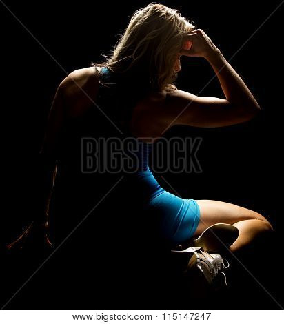 Woman Sitting In Blue Outfit Highilighted From Back
