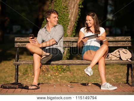 Young Couple Having Fun On A Bench In Park While Socializing Over Web