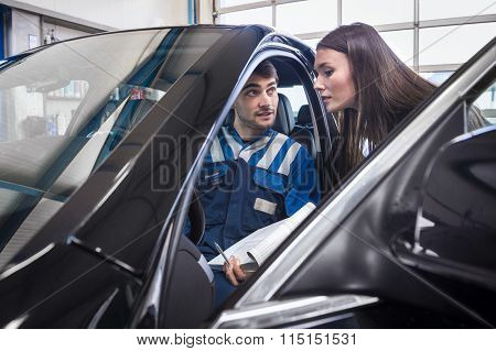 client gets explanaition from the car mechanic over the serviced items of her car. The mechanic sits in the car and points to the dashboard.