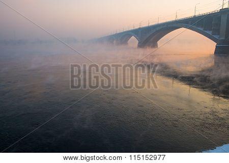 Winter river with vapors of the Municipal bridge at sunset in city Krasnoyarsk,Russia