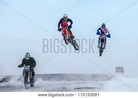high jumps and flight riders on motorcycle at winter motocross